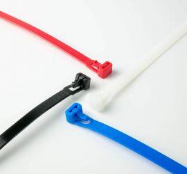Een witte, een zwarte, een rode en een blauwe hersluitbare kabelbinder op een witte achtergrond.