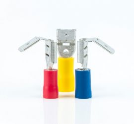 A red, a yellow and a blue insulated piggyback connector, without sleeve, standing upright, on a white background.